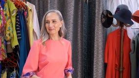 Zadowolona dojrzała kobieta beszcześci w nowej sukni w odzieżowym sklepie Rozochocona starsza kobieta próbuje suknię w trafnym po zbiory