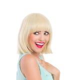 Zadowolona i uśmiechnięta blond dziewczyna patrzeje daleko od Obrazy Royalty Free