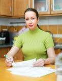 Zadowolona kobieta patrzeje przez rachunków Zdjęcia Stock