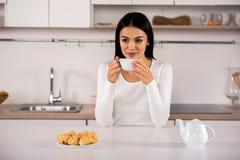 Zadowolona kobieta pije herbaty w kuchni zdjęcie royalty free
