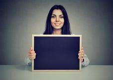 Zadowolona kobieta pokazuje pustego blackboard fotografia stock
