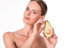 Zadowolona młoda kobieta trzyma część avocado Zdjęcia Royalty Free