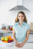 Zadowolona młoda kobieta pozuje w kuchni Obrazy Royalty Free