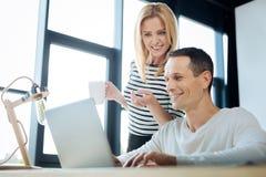 Zadowolona pozytywna kobieta wskazuje przy laptopu ekranem Fotografia Stock