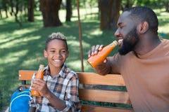 Zadowolona radosna chłopiec trzyma butelkę z napojem obraz stock