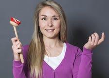 Zadowolona 20s dziewczyna ono zgadza się dla czyści naczyń dla zabawy Obrazy Royalty Free