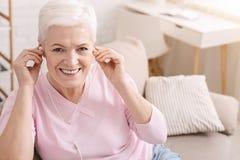Zadowolona starzejąca się kobieta słucha muzyka w domu zdjęcie royalty free