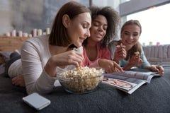 Zadowolone zaangażowane dziewczyny patrzeje magazyn Obrazy Stock