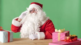 Zadowolony Święty Mikołaj mówi na telefonie, śmia się, siedzi przy stołem z prezentami, zielony chromakey w tle zdjęcie wideo