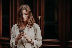 Zadowolony zadowolony żeński młodzieniec ogląda wideo na mądrze telefonie, czyta bankowości powiadomienie, ubierającego w białym  zdjęcie stock