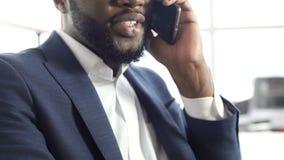 Zadowolony afroamerykański mężczyzna opowiada na telefonie komórkowym w kostiumu, robi spotkaniu zbiory wideo