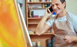 Zadowolony artysta używa telefon komórkowego w obrazu studiu obraz stock