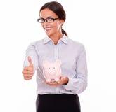 Zadowolony bizneswomanu mienia menchii prosiątka bank Zdjęcia Stock