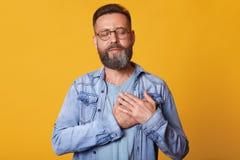Zadowolony brodaty mężczyzna z zamkniętymi oczami, utrzymuje ręki na klatce piersiowej, ubierającej w modnej drelichowej kurtce,  obraz stock