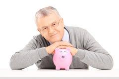 Zadowolony dojrzały dżentelmen pozuje nad prosiątko bankiem Zdjęcia Stock