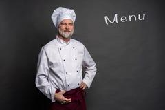 Zadowolony dojrzały szef kuchni patrzeje pewnie przy śmiać się i kamerą Fachowy podej?cie biznes obrazy royalty free