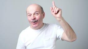 Zadowolony dorośleć mężczyzny pokazuje palec wskazującego w górę, dawać radzie zbiory wideo