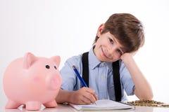 Zadowolony dziecko kalkuluje jego oszczędzania obraz royalty free