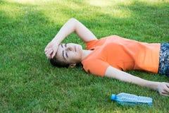 Zadowolony dziewczyny obsiadanie w parku po treningu zdjęcie stock