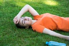 Zadowolony dziewczyny obsiadanie w parku po treningu zdjęcia stock