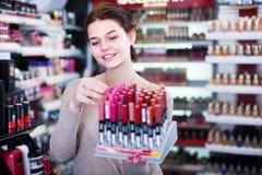 Zadowolony kobieta klient decyduje na makijaż rzeczach w kosmetykach obraz royalty free
