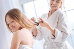 Zadowolony kobiety czesać długie włosy jej dzieciak Obrazy Stock