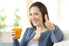 Zadowolony konsument trzyma sok pomarańczowego szklany obrazy royalty free