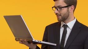 Zadowolony mężczyzna pokazuje ok i mruga, badający nowe zastosowanie na jego laptopie zbiory