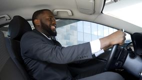 Zadowolony mężczyzna w garnituru obsiadaniu w samochodzie, pomyślny zakup, szczęście fotografia stock