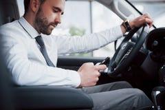 Zadowolony młody biznesowy mężczyzna patrzeje telefon komórkowego podczas gdy jadący samochód zdjęcia stock