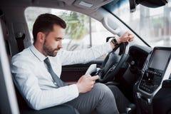 Zadowolony młody biznesowy mężczyzna patrzeje telefon komórkowego podczas gdy jadący samochód fotografia royalty free