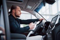 Zadowolony młody biznesowy mężczyzna patrzeje telefon komórkowego podczas gdy jadący samochód zdjęcie stock