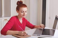 Zadowolony piegowaty imbirowy żeński uczeń przygotowywa informację dla konwersatorium, pisze puszek informaci w notatniku od lapt fotografia stock