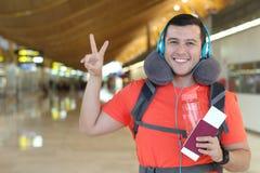 Zadowolony podróżnik daje pokoju znakowi od lotniska obrazy stock