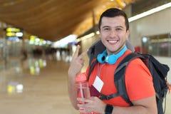 Zadowolony podróżnik daje pokoju znakowi od lotniska obrazy royalty free
