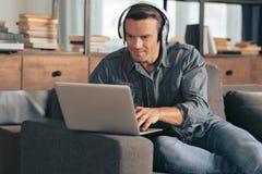 Zadowolony pozytywny mężczyzna używa jego laptop fotografia stock