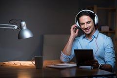 Zadowolony radosny młody człowiek słucha muzyka zdjęcia royalty free