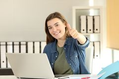 Zadowolony stażysta z aprobatami przy biurem zdjęcia stock