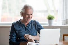 Zadowolony stary mężczyzna patrzeje ekran komputerowego siedzi w domu obraz stock