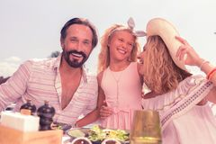 Zadowolony szczęśliwy rodzinny obsiadanie wpólnie przy stołem zdjęcie stock