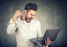 Zadowolony zwycięski mężczyzna z laptopem obrazy stock