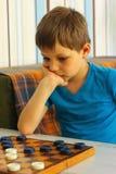 Zadumana chłopiec podczas gry warcaby fotografia royalty free