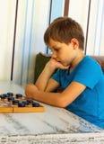 Zadumana chłopiec podczas gry warcaby fotografia stock