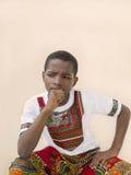 Zadumana chłopiec sadzająca przed ścianą, dziesięć lat Obraz Stock