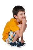 Zadumana chłopiec w żółtej koszula zdjęcia royalty free