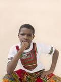Zadumana chłopiec sadzająca przed ścianą, dziesięć lat Obrazy Royalty Free
