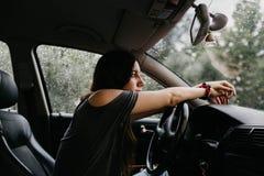 Zadumana i smutna młoda kobieta z rękami na kierownicie samochód na deszczowym dniu zdjęcia royalty free