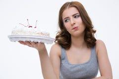 Zadumana kobieta patrzeje tort Zdjęcia Royalty Free