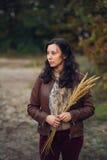 Zadumana kobieta z wiązką od jesieni rośliny w rękach Zdjęcia Royalty Free