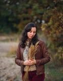 Zadumana kobieta z wiązką od jesieni rośliny w rękach Obraz Stock